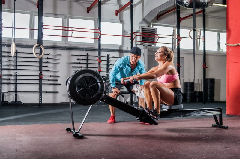 Girl training on row machine with assistance of trainer at gym