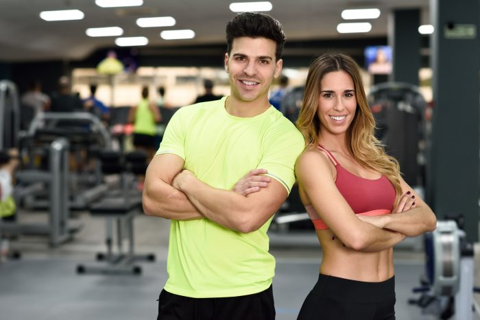 Man and woman personal trainers in the gym
