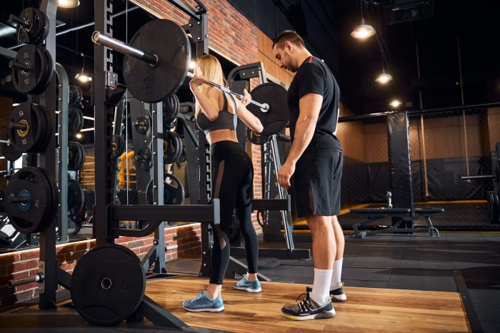 Personal trainer assisting woman at the gym